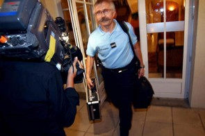 Police carrying bags leave the Astana team hotel