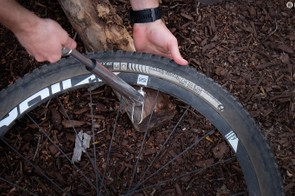 When possible, support the pump head against a log or rock. Not only does this lessen the stress on the valve stem, it also gives you something to push again when inflating your tyre