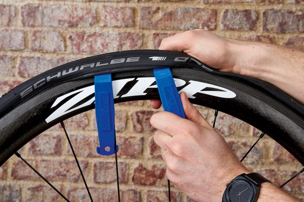 Use a tyre lever – or two, if required – to lift one side of the tyre off the rim.