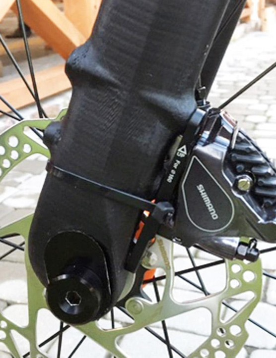 The flat-mount on the front fork is incredibly minimal with the anchor bolts piercing all the way through the fork leg