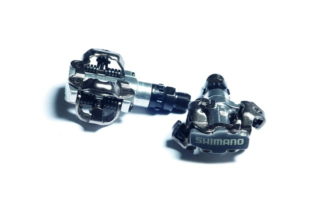 You may want to consider starting with mountain bike pedals, which have a two-bolt pattern but can be used with mountain bike or commuter shoes, which are much easier to walk in than stiff road shoes