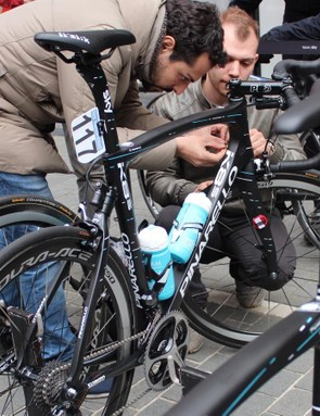 HiRide co-founder Domenico Borgese and an assistant remove the remote switch and wire before the start of Scheldeprijs