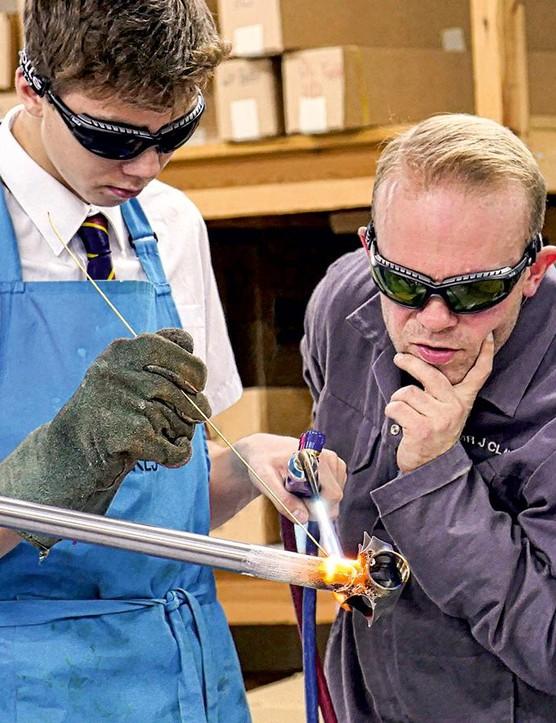 Teacher Jon Kaye keeps a close eye as a pupil flies solo with the torch on a bottom bracket shell
