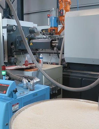 This large white hopper contains the polyamide for the rollers, and the small hopper sitting on top of the machine provides the Tacx's blue colour