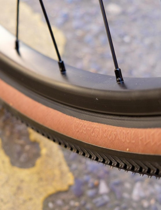 Large, square section rims are paired to 42mm own-brand tyres. Digging the tan wall action too