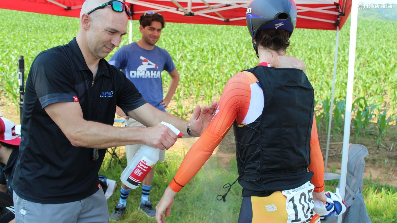 Henderson sprays Stevens' arms, torso and legs with rubbing alcohol right before the start for its cooling effect