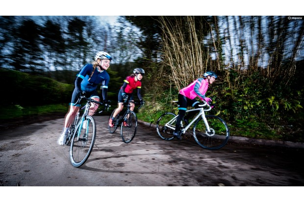 Three women riding road bikes on a tree-lined road