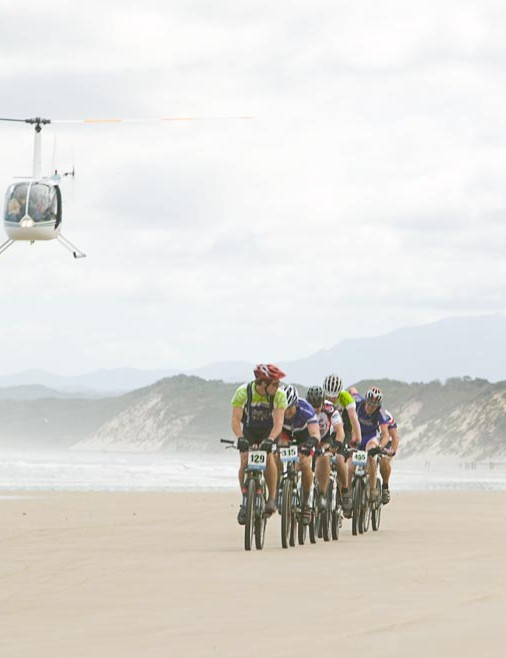 A media helicopter gets a great view of riders streaming along Ocean Beach