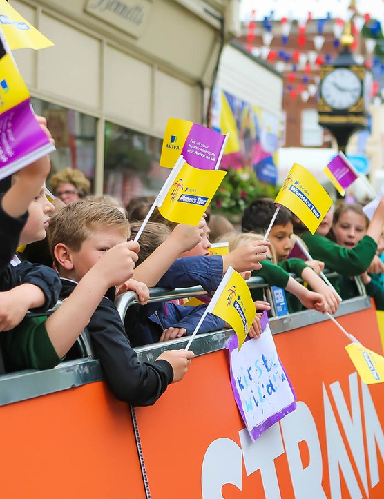 Schoolchildren lined the route, with many holding homemade signs and flags, ready to cheer on their favourite riders