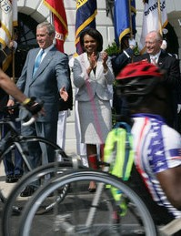 President Bush and Secretary of State Condoleeza Rice applaud the riders on their way