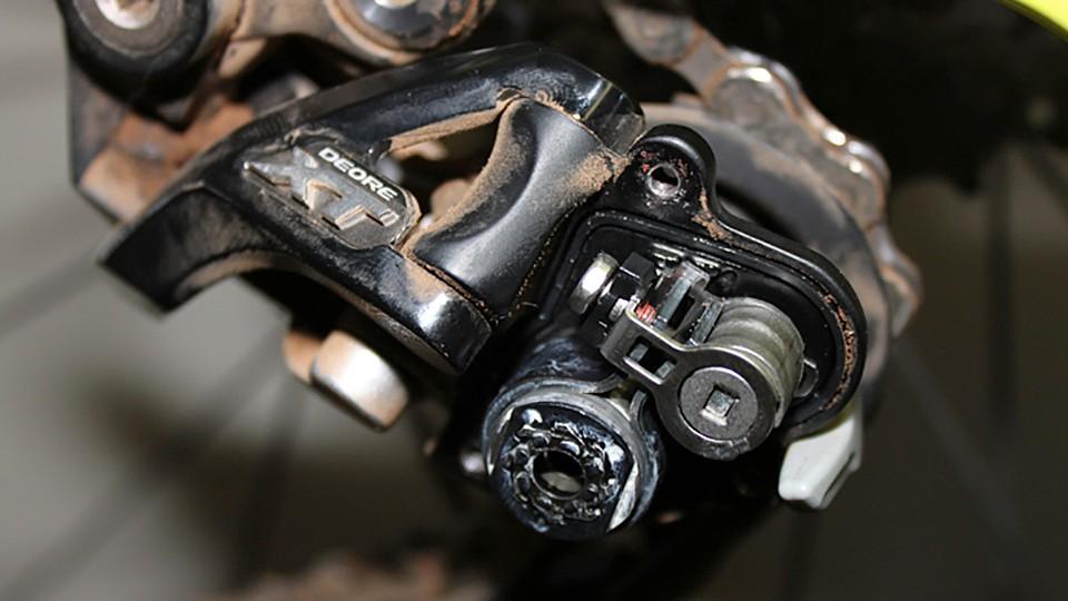 Shimano XT and SLX Shadow Plus rear derialleurs have a non-removable brace that reinforces the cam mechanism