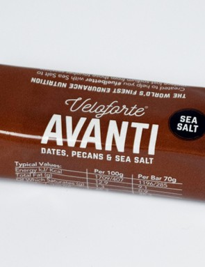 Photograph of a fruit and nut bar wrapped in foil and brown paper on a white background