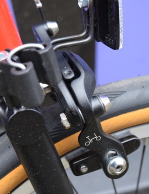 Detail photograph of the brake calipers on the Brompton bicycle showing a tiny white logo on a black background