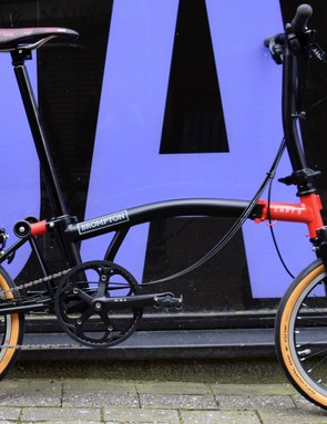 Picture of the side of a black and red folding Brompton bicycle against a blue and black background