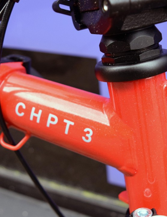 Detail of the red frame of a Brompton folding bicycle with CHPT 3 written in white