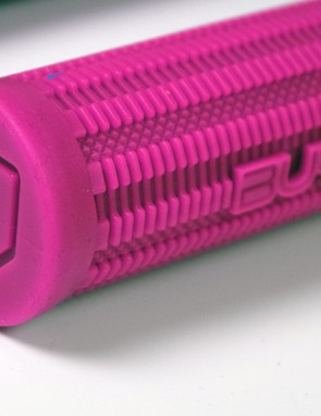 Detail of the end of a textured rubber handlebar grip in pink on a white background