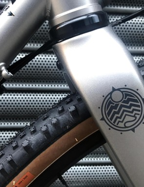 Detail of the top of the forks on the Norco adventure bike, which are silver with a logo of the sun over mountains picked out in black