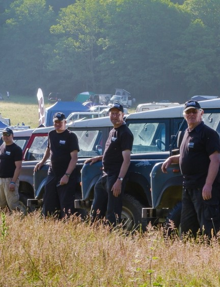The fleet of Land Rovers and their drivers who speed racers to the top of the hill