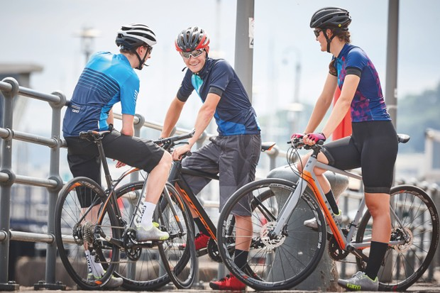 Road cyclists chatting by harbourside