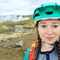 Photograph of Aoife Glass wearing a turquoise helmet and standing in front of a fumerole in Iceland