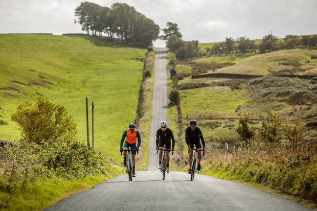 Group of three road cyclists riding up a hill on a country lane