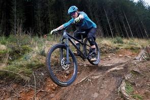 male cyclist riding black hardtail mountain bike through woodland