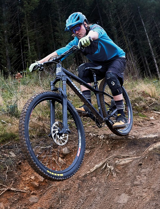 male cyclist riding black hardtail mountain bike through woodland