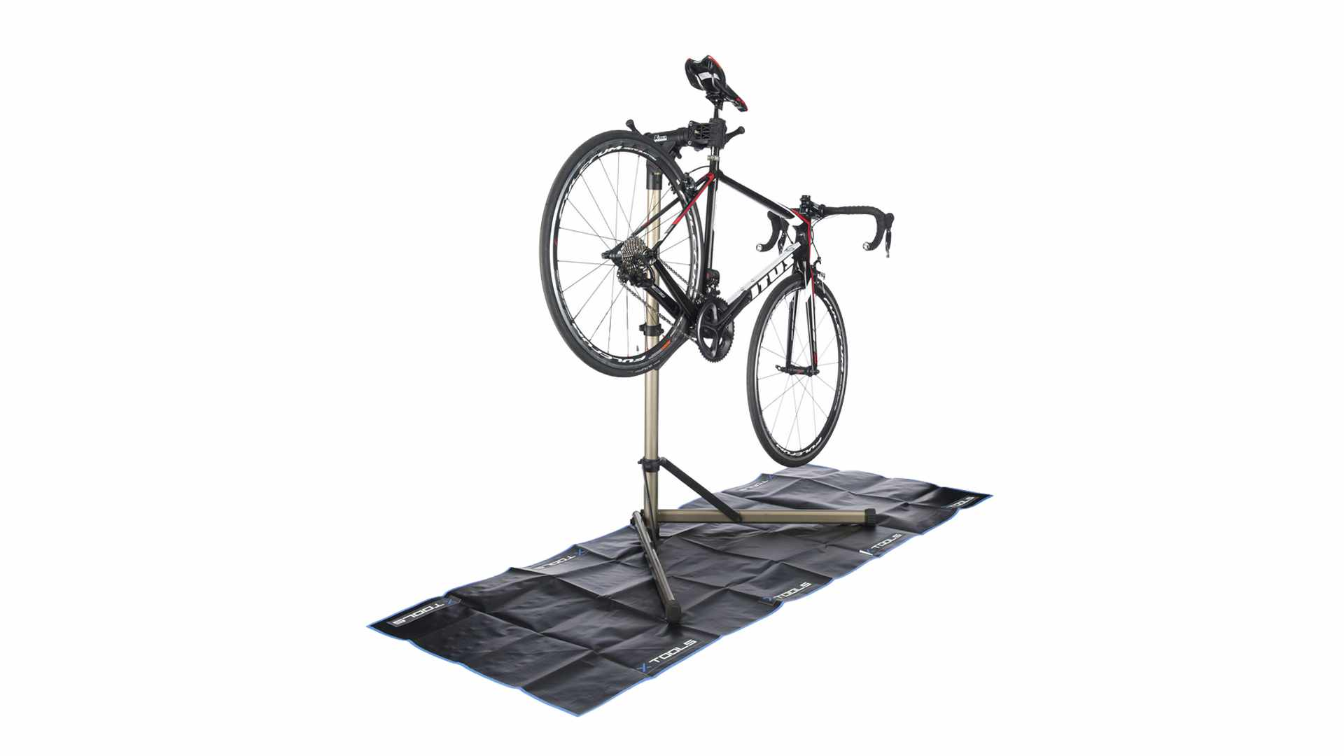 Photograph of a bike held up in a bike stand on a black matt