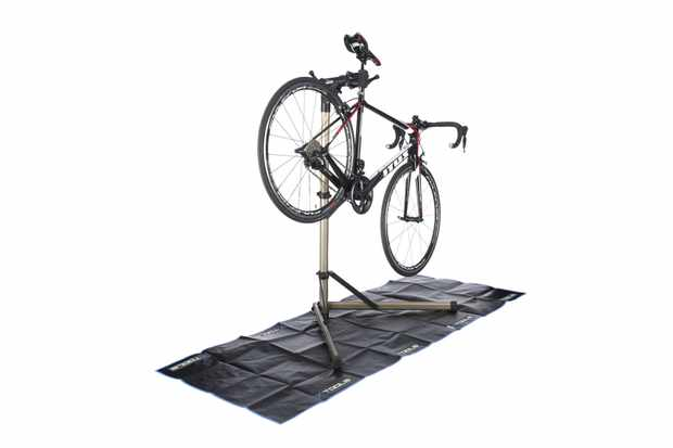 Photograph of a bike held up in a bike stand on a black matt