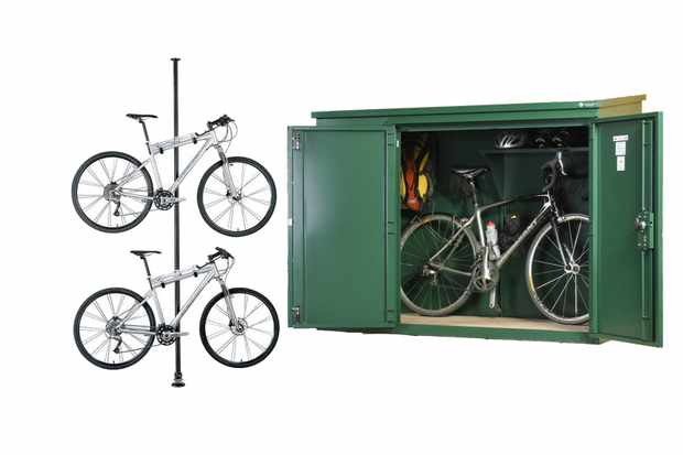 Photo of a bike stand with two bikes in it and a green metal bike shed on a white background