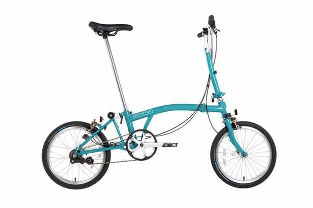 A photography of a light blue Brompton folding bicycle on a white background