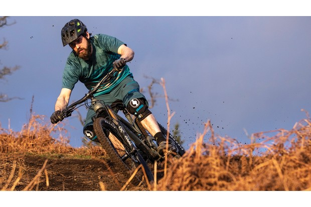 Male cyclist riding full-suspension mountain bike in woodland