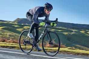 male cyclist rides black road bike countryside