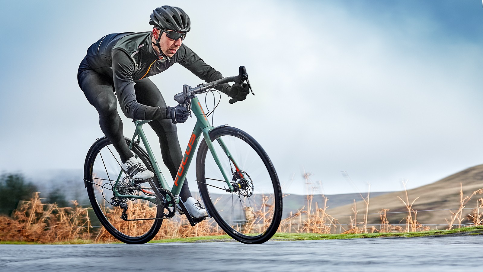 male cyclist riding green bike through country side