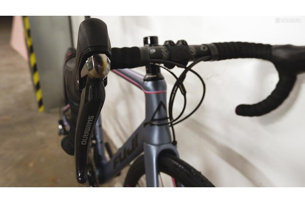 Close-up detail of the handlebars, brake levers and gear shifters on the Fuji Supreme 2.3 road bike