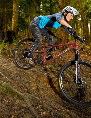 A woman in a blue top riding over roots downhill in a forest