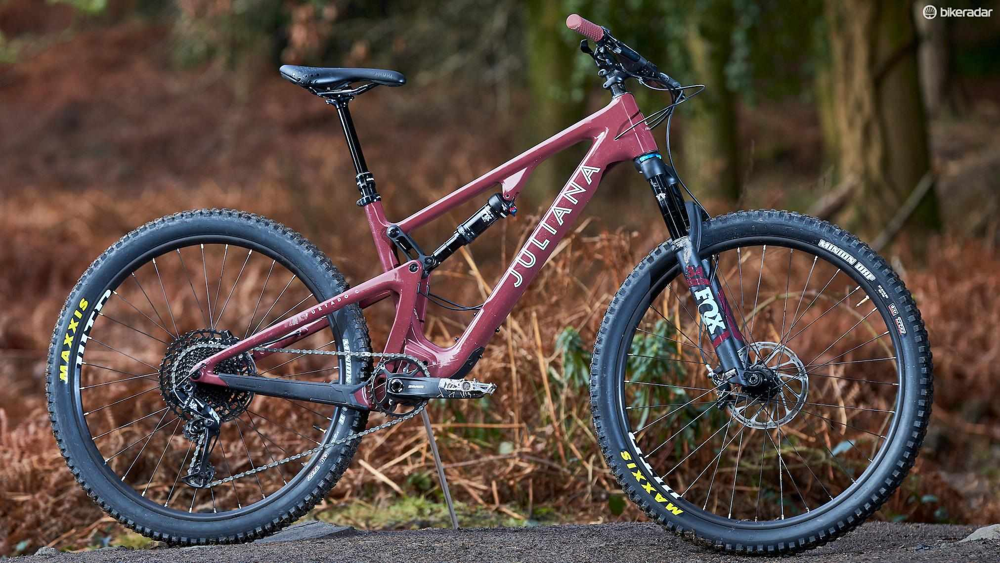 A side-on photograph of the dark red Juliana Furtado mountain bike standing in a forest