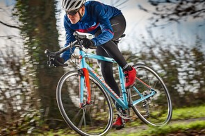 male cyclist riding blue bike in woods
