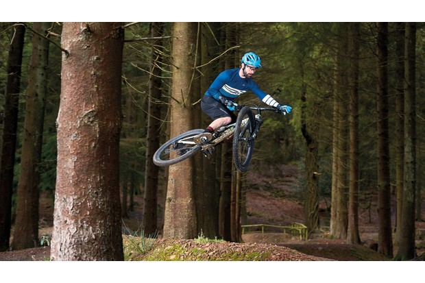 Male cyclist riding mountain bike woodlands