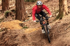 male cyclist riding orange full suspension mountain bike in woodland