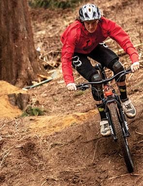 male cyclist riding orange full suspension mountain bike in woodland