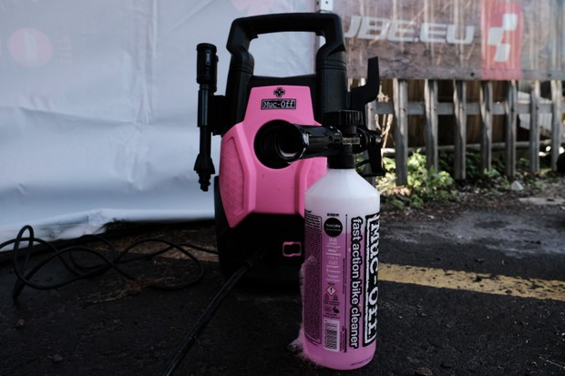 Muc-Off pink and black pressure washer with a bottle of Muc-Off