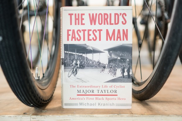 Cycling book, The World's Fastest Man by Major Taylor, between two bike wheels