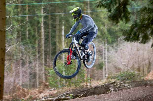 Alex Evans riding an Orange Stage 6 over a jump at Cannop, Forest of Dean, Gloucestershire. March 2019