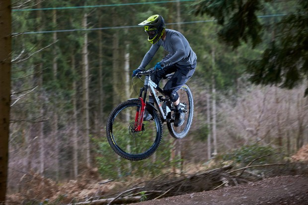 Alex Evans riding an Orange Stage 6 over a jump at Cannop, Forest of Dean, Gloucestershire. March 2019.