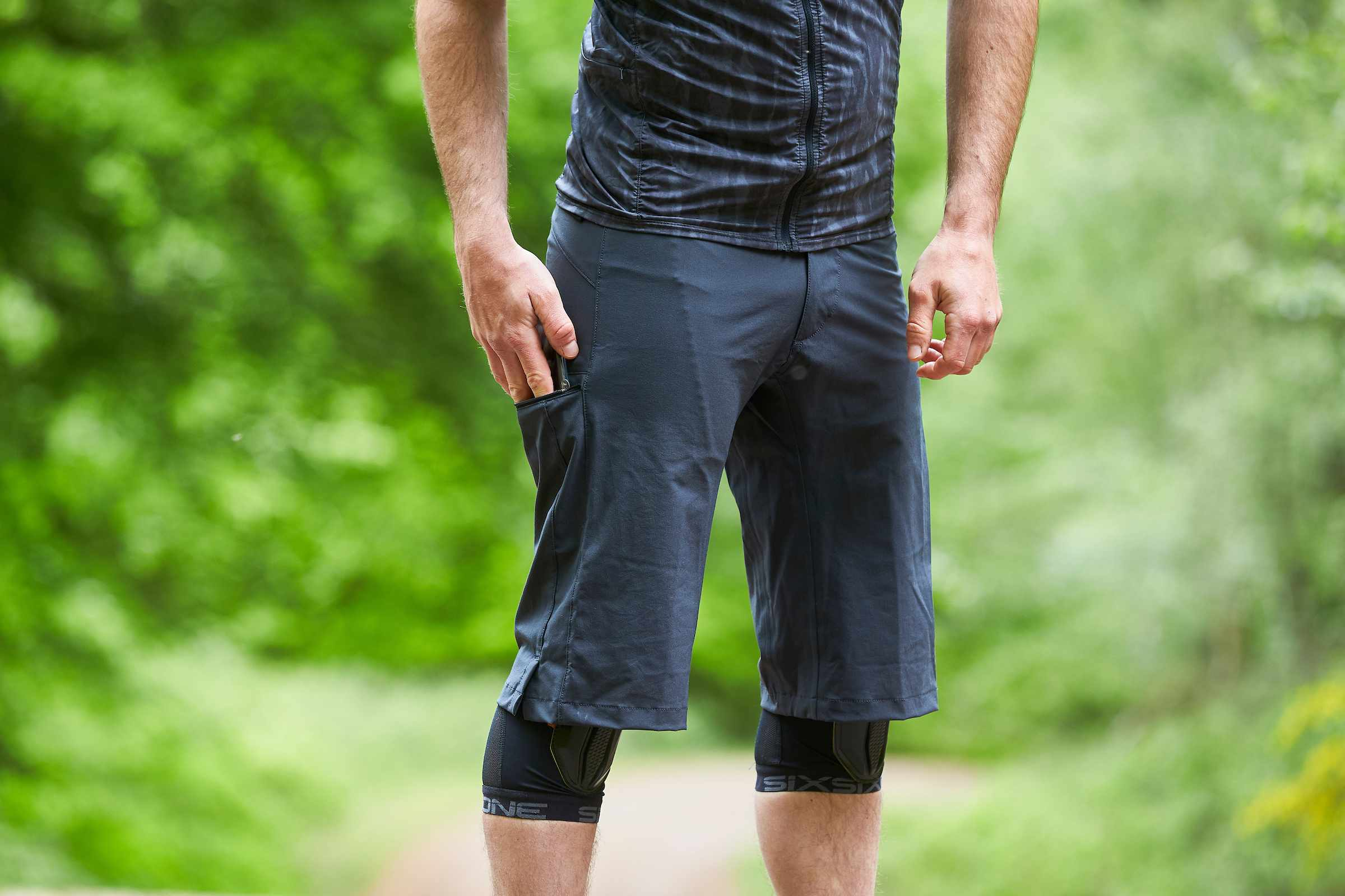 Man wears Mission Workshop The Traverse shorts with one hand in right hand pocket