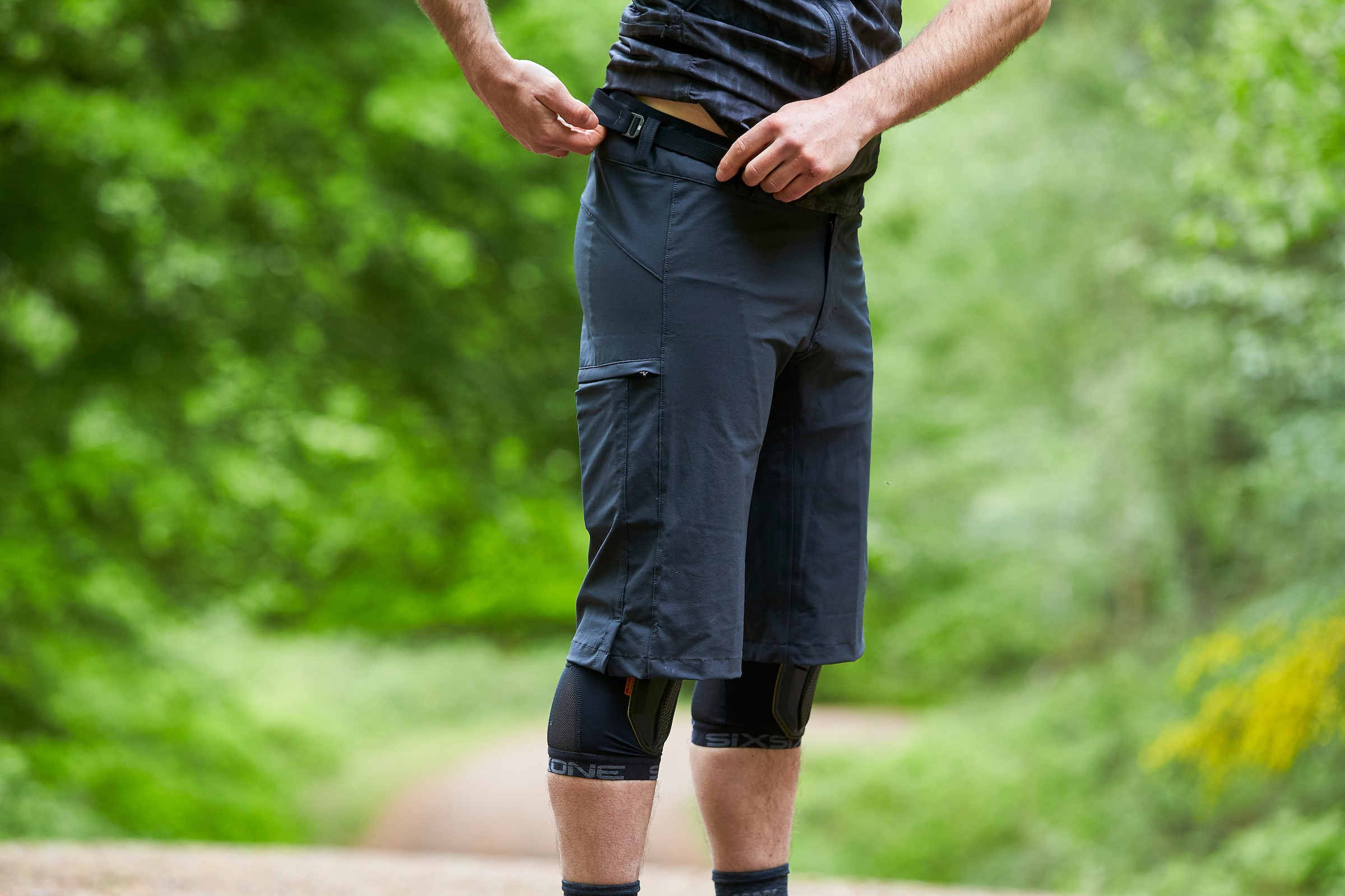 Man tightens belt clasp on Mission Workshop The Traverse shorts