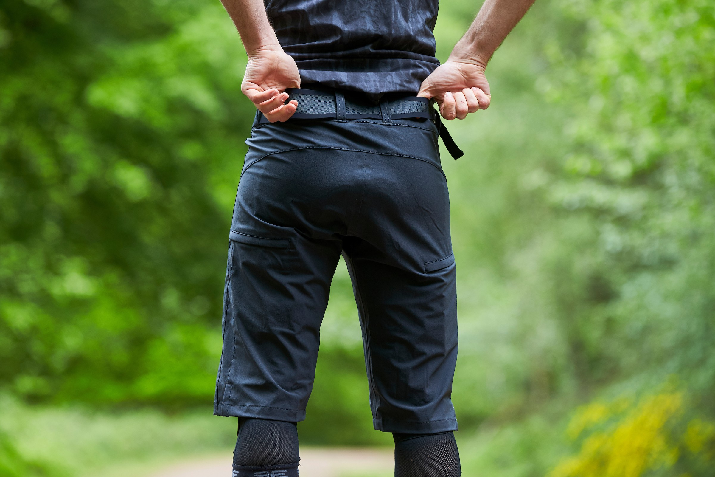 Man adjusted waistband on Mission Workshop The Traverse shorts with his hands