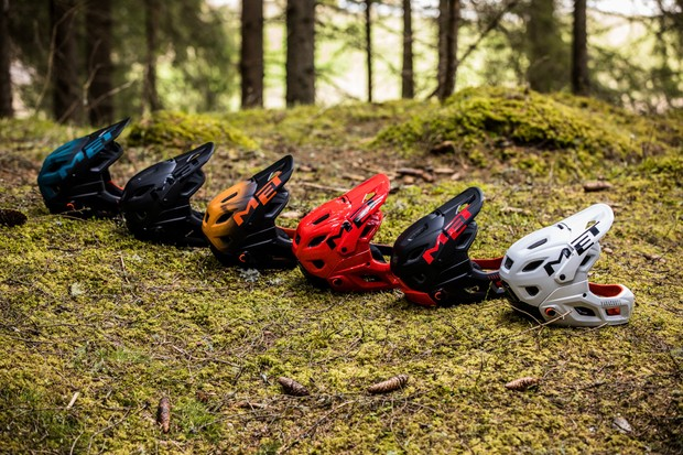 A selection of different colours of the MET Parachute MCR helmet laid out in woodland