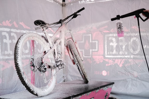 Bike in a stand being sprayed with white cleaning foam from the Muc-Off pressure washer